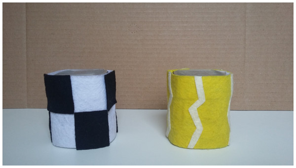 Two of the cups and felt sleeves in front of the occluder used in Experiment 2.