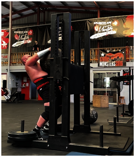 An athlete performing the atlas stone lift.